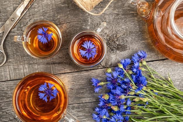 Чашки травяного чая, прозрачный чайник и цветы синих васильков