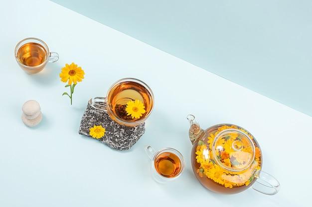 허브 차 한잔, 금송화 꽃과 파란색 배경에 돌이 있는 투명한 찻주전자. 금송화 차는 건강 개념에 도움이 됩니다. 복사 공간