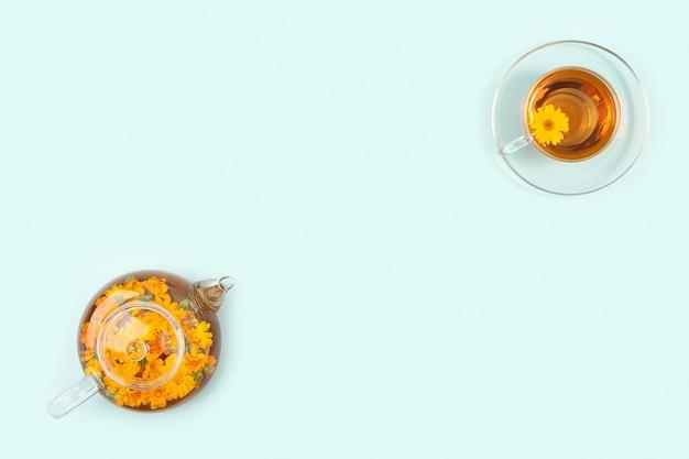 Чашки травяного чая, прозрачный чайник с цветами календулы на синем фоне. концепция успокаивающего напитка. копирование пространства плоская планировка вид сверху.