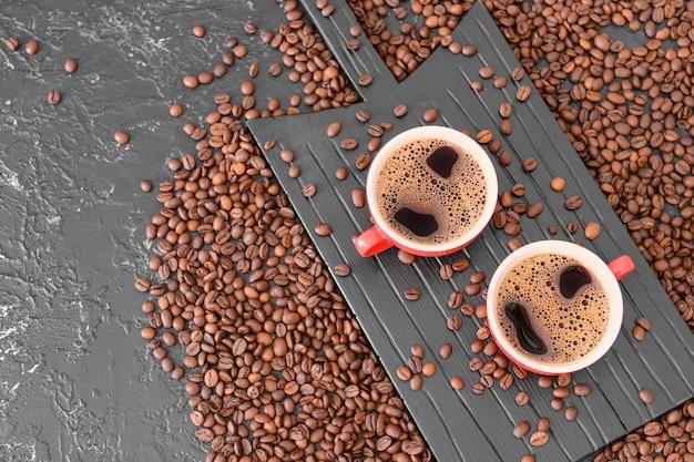 Чашки горячего кофе и бобов на столе
