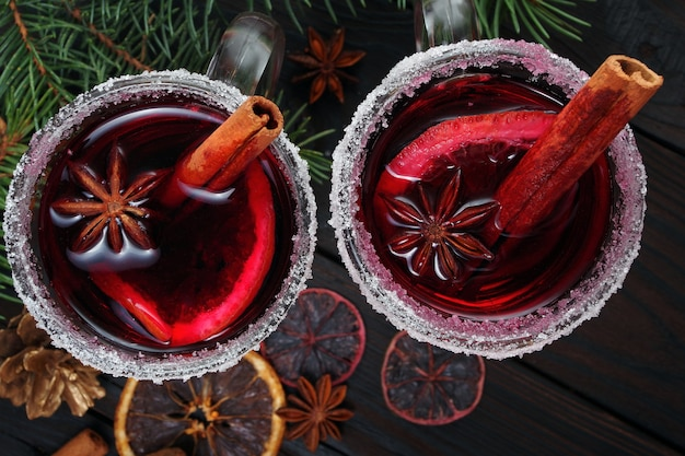 Mulled 와인 향신료와 나무 테이블 위에 건조 감귤류 과일의 컵 온난화 크리스마스 음료를 닫습니다.