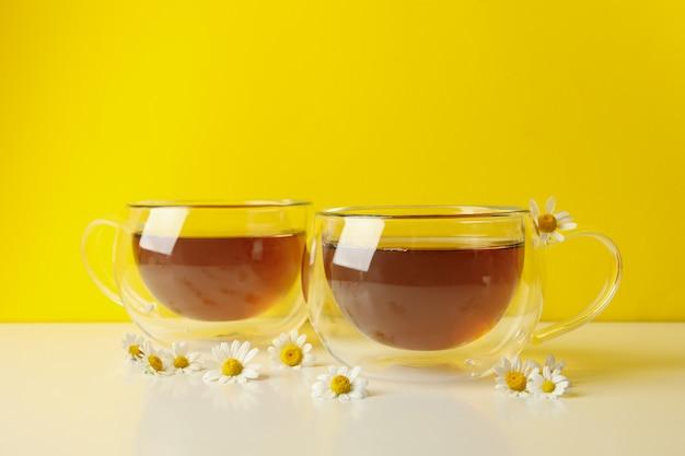 お茶と黄色の背景に白いテーブルにカモミールのカップ