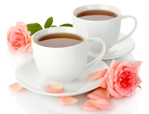 白で隔離のバラとお茶のカップ