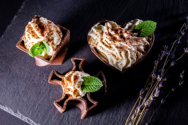 Cups printed on a 3d printer with chocolate, whipped cream and mint leaves