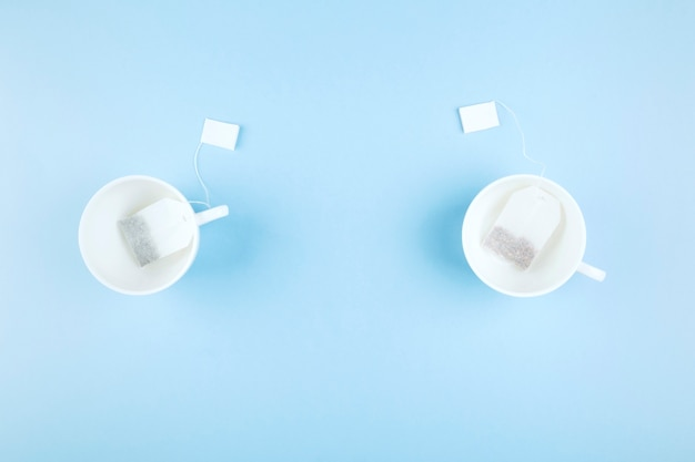 Cups of tea and tea bags on blue background. top view, copy space. food background