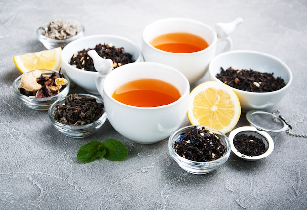 Cups of tea with aromatic dry tea in bowls