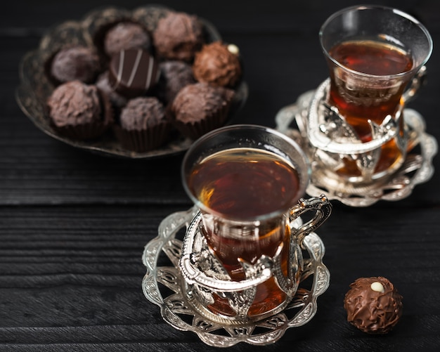 Cups of tea with truffles and wooden background
