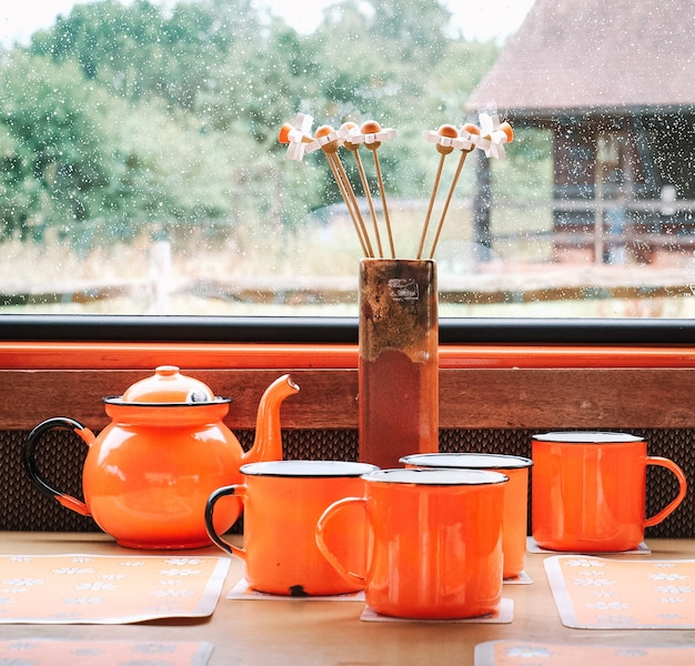 Cups and a teapot next to flowers in front of the window during a rainy day