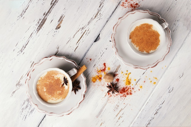 Cups of traditional indian chai tea with star anise and cinnamon
