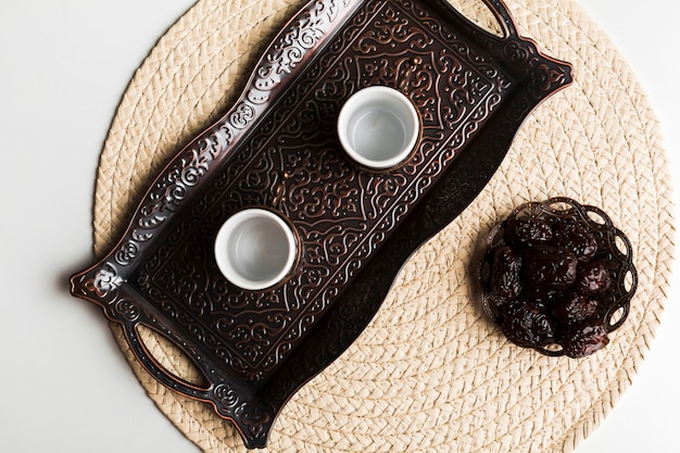 Cups on tray near saucer with sweet prunes on mat