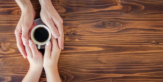 Чашки с кофе в руках мужчин и женщин