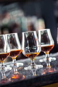 ナイトクラブのバーカウンターでコニャックラムブランデーまたはウイスキードリンクを飲みながらカップ。