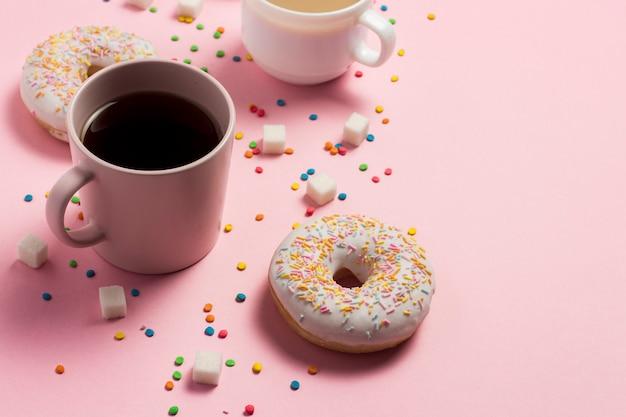 コーヒーや紅茶、ピンクの背景に新鮮なおいしい甘いドーナツとカップ。ファーストフードのコンセプト、ベーカリー、朝食、お菓子、コーヒーショップ。フラット横たわっていた、トップビュー、コピースペース。