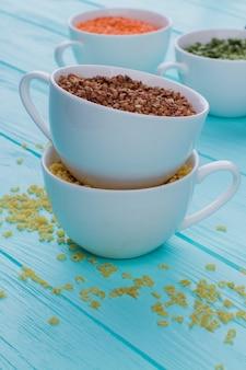 乾燥そばやその他のシリアルが入ったカップ。青い木製のテーブルに散らばった穀物。