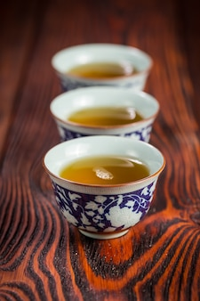 Cups with green tea on wood