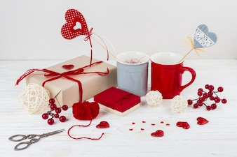 Cups with hearts on wands near little hearts, scissors and presents