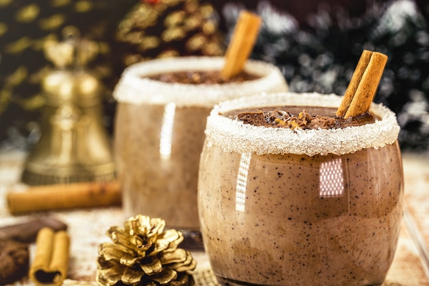 ホットチョコレート、シナモン、砂糖、ミルク、スチームスモーク、ホットクリスマスドリンクのカップ