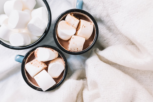 Cups with hot cocoa and marshmallows on table
