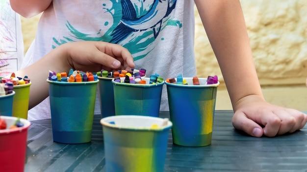 テーブルの上に色とりどりの鉛筆がたくさん入ったカップ2人の子供が鉛筆を選ぶ