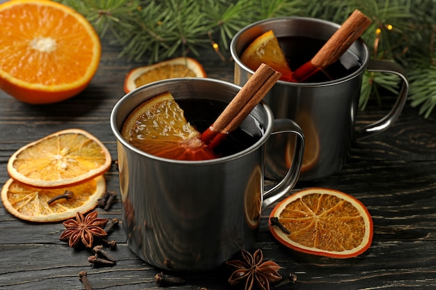 Cups with mulled wine, ingredients and pine branches on wooden