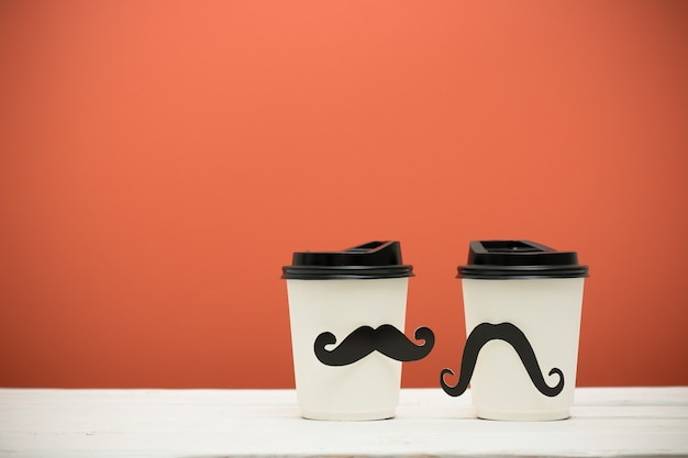 Cups with mustache on table on orange background. vintage filter.