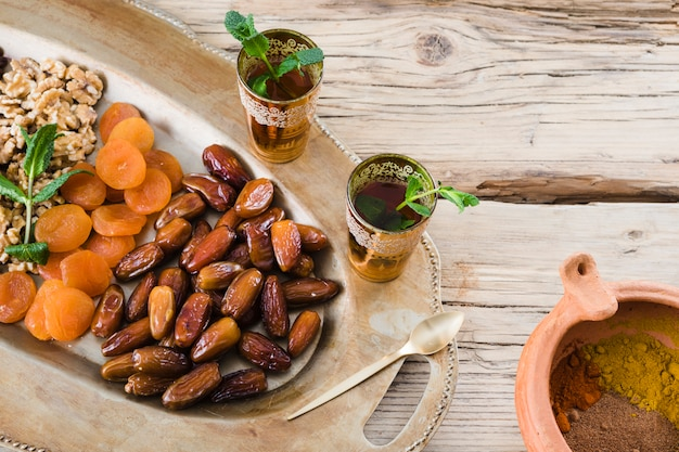 Cups with plant twigs near bowl with spices and dried fruits and nuts on tray