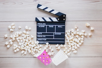 Cups with popcorn and clapboard