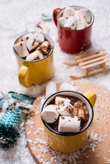 Cups with sweet candies and beverages near christmas toys between snow
