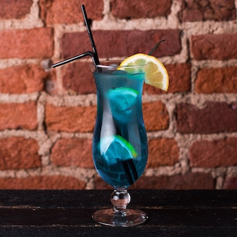 Curassao blue cocktail with lemon in a glass goblet