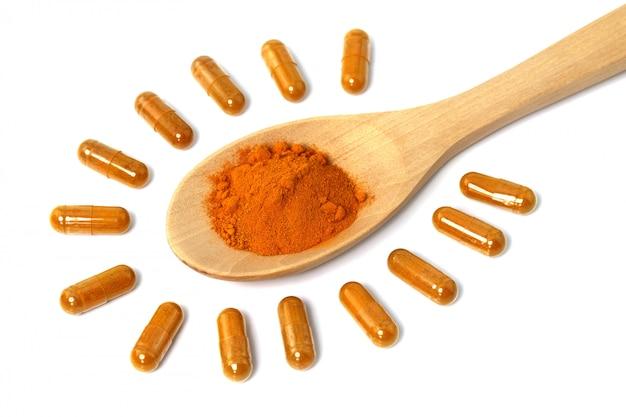 Порошок куркумы (curcuma longa l.) или curcuma longa с капсулой для нетрадиционной медицины, изолированный на белой стене, продукты spa и пищевой ингредиент, капсула herb.