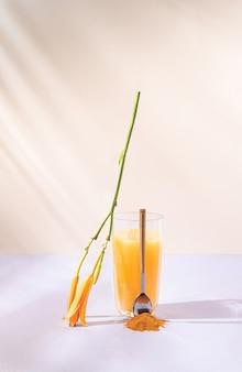 パステルベージュと紫の背景にウコンまたはオレンジジュース。夏のリフレッシュドリンク。最小限の自然と食べ物のコンセプト。