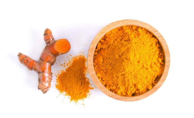 Curcuma powder in a bowl and root on white background