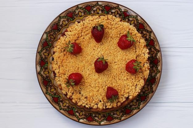 白い表面のクローズアップのプレートに配置されたイチゴと豆腐ケーキ、上からの眺め