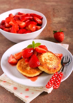 Curd cheese fritters with strawberry on plate