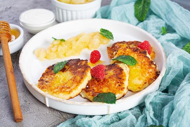 사워 크림, 꿀, 딸기를 곁들인 커드 치즈 팬케이크. 캐러멜 처리된 배를 곁들인 맛있는 시르니키