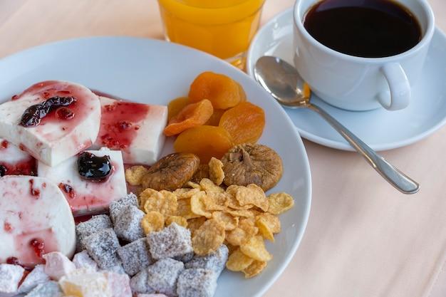 두부 치즈는 과일 요구르트, 말린 살구, 무화과, 콘플레이크 및 컵 커피를 테이블에 부었습니다. 아침 식사 개념입니다. 확대 프리미엄 사진