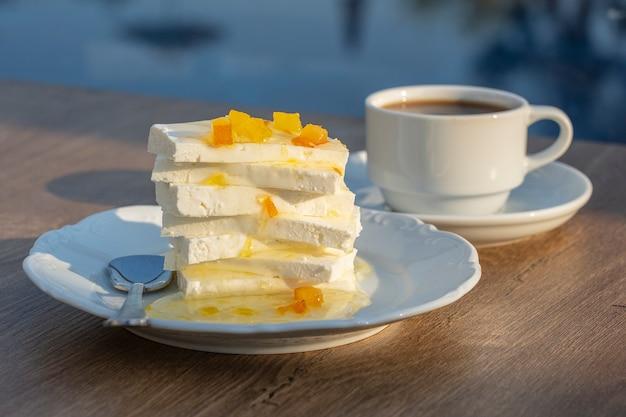 テーブルの上にレモンジャムとカップコーヒーと豆腐チーズ。朝食のコンセプト。閉じる