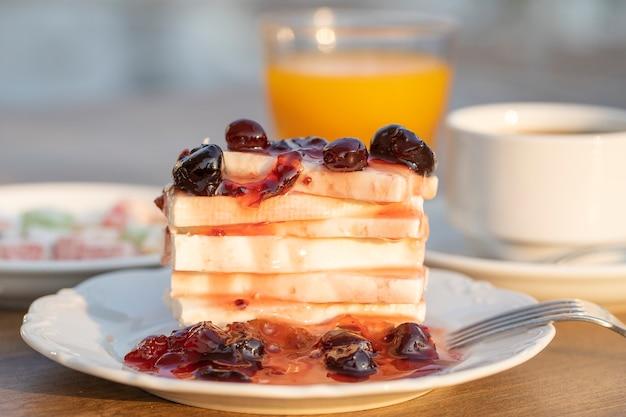 レッドチェリージャム、オレンジジュース、テーブルの上のカップコーヒーと豆腐チーズ。朝食のコンセプト。閉じる