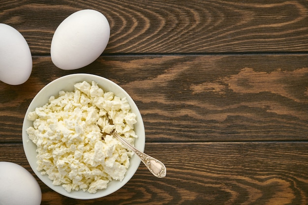 Curd and eggs on wooden table, dairy products