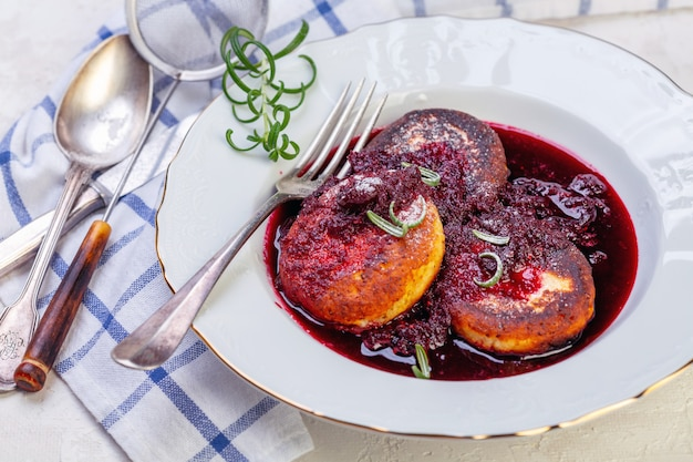 Curd fritters with cherry sauce with rosemary