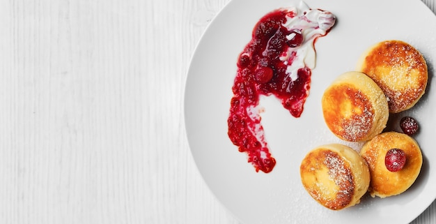 Творожные оладьи или сырники, посыпанные сахарной пудрой со сливками и клюквенным джемом