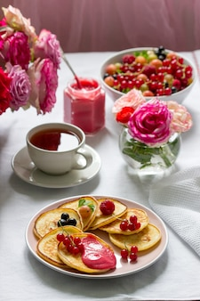 Curd pancakes with berry curd served with tea on a table decorated with bouquets of roses. Premium Photo