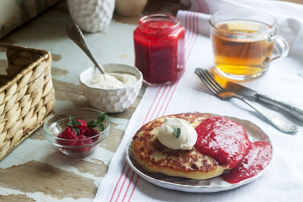 Curd pancakes with strawberry sauce, sour cream and raspberries, and herbal tea on a light table