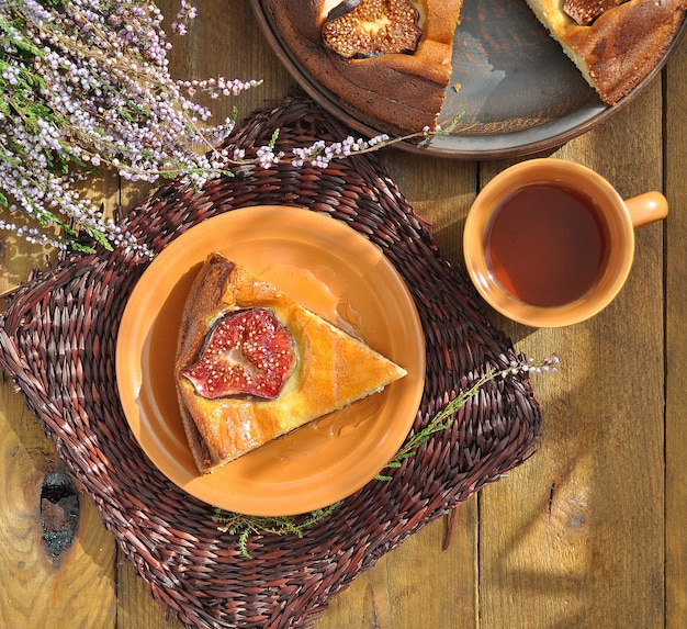 Curd pudding with figs and honey on wicker brown napkin and herbal tea with heather on the wooden background