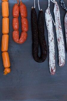 Вяленое мясо и колбасы, висящие на стойке на рынке, вертикальный снимок