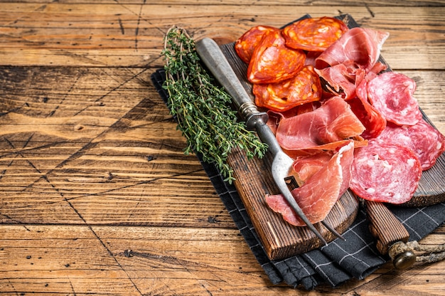 Cured meat platter served as traditional spanish tapas. salami, jamon, choriso sausages on a wooden board. wooden background. top view. copy space.