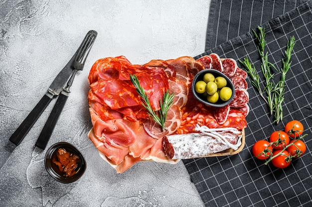 Cured meat platter of traditional spanish tapas. chorizo, jamon serrano, lomo and fuet. gray background. top view