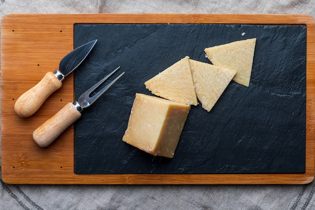 Cured sheep chees on a wooden board and black slate
