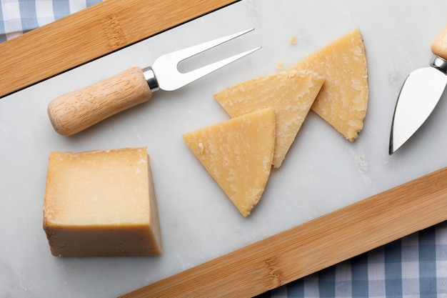 Вяленый овечий сыр. нарезать на кусочки по белому мрамору. вилка и нож для сыра. вид сверху.