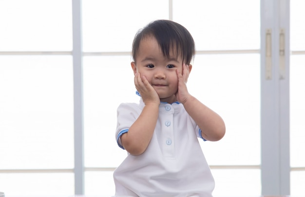 Curiosity asian toddler lovely girl naughty cheerful play alone in father home office, smiling adorable daughter looking camera with happy sitting on table with office stationary background, happy kid